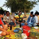 Thai family eating next to the beach in Rayong town