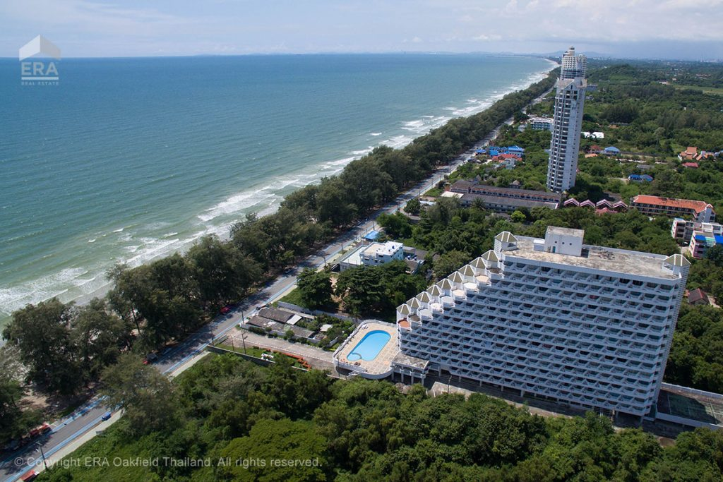 Drone view of condominium building next to beach in Rayong, Thailand