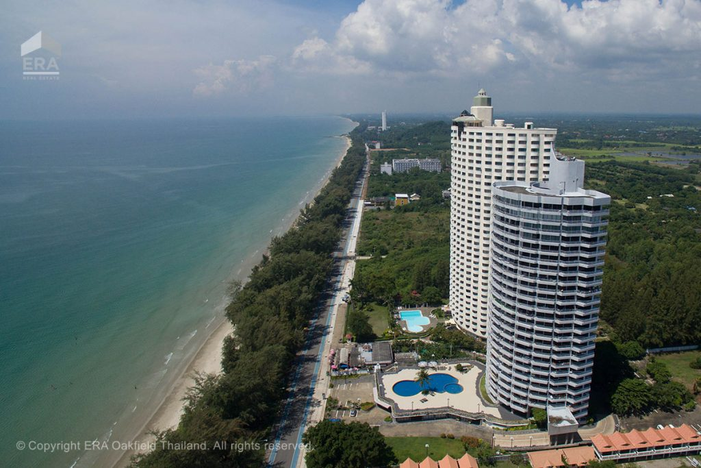 Drone view of condominium building next to mae ramphung beach